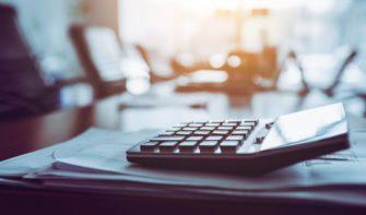 Close up calculator on business working desk, dark background.
